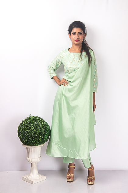 A Mint-Green Kurta Set that has an Asymmetric work on the yoke. The drape falls from the shoulder. The sleeves are detailed with thread and sequins embroidery